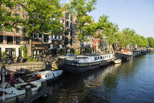 Photo  On the banks of the canals of Amsterdam, magnificent boats are transformed into