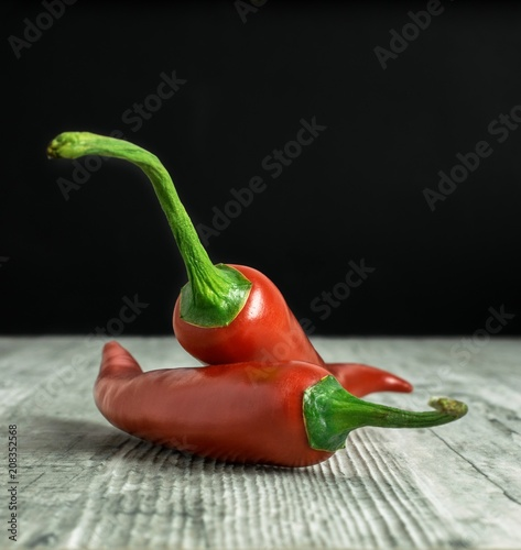 Fotobehang Kruiderij Red chili peppers on a rustic wooden surface with dark background copy space for your text