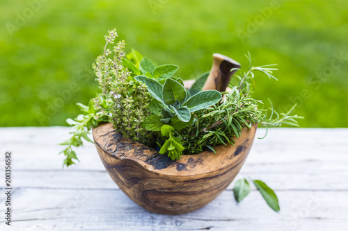 Photo  Fresh and aromatic herbs in a wooden mortar.