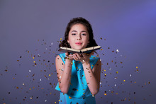 Young Woman Or Teen Girl Is Blowing Glitter Confetti.Asian Girl Teenager Holds Book In Hands,on Purple Background Festive Sparkles For The Party Are Flying.Concept Christmas,new Year,holiday,birthday.