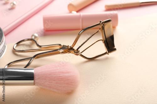 Brush for applying makeup and eyelash curler on color background, closeup Wallpaper Mural