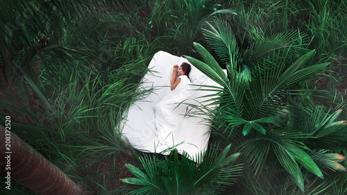 Foto op Canvas Spa A hidden place. Sleeping woman in deep jungle forest lies on airbed,View from above
