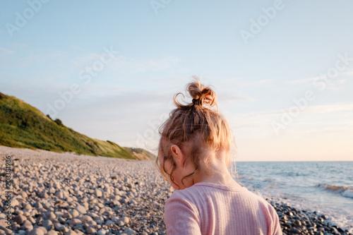 Kleines Mädchen läuft bei Sonnenuntergang am Strand entlang