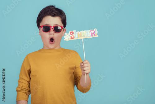 Valokuva Summer, niño gracioso con gafas de sol sobre fondo azul
