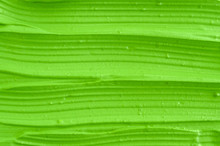 Green Cosmetic Clay (facial Mask, Cream) Texture Close Up, Selective Focus. Abstract Electric Lime Green Background With Stripes.