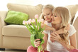 Portrait of cute little girl and her mother with tulip bouquet at home
