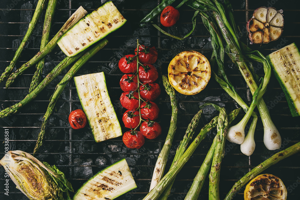 Fototapety, obrazy: Grilled vegetables green asparagus, garlic, lemon, spring onion, zucchini, cherry tomatoes, salad on bbq grill rack over charcoal. Top view. Barbecue concept
