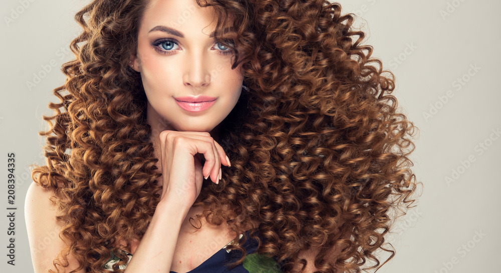 Fototapeta Brunette  girl with long  and   shiny curly  hair .  Beautiful  model woman  with wavy hairstyle