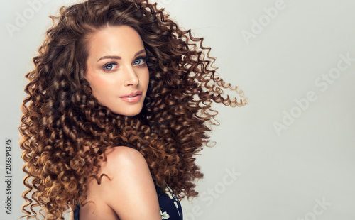 Obraz Brunette  girl with long  and   shiny curly  hair .  Beautiful  model woman  with wavy hairstyle