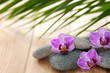 Spa stones with orchid flowers on wooden table