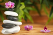 Stack of spa stones with beautiful orchid flower on blurred background