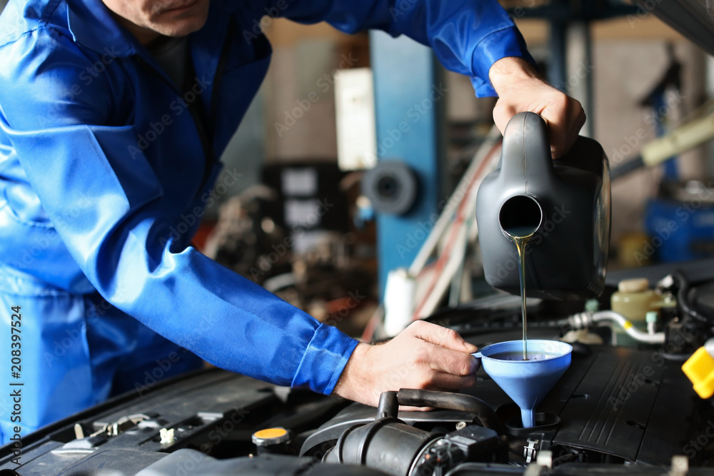 Fototapety, obrazy: Male mechanic refilling car oil in service center
