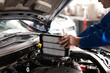 Male mechanic examining car in service center