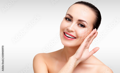 Fotografie, Obraz  Closeup shot of female pretty face with white arrows on skin for cosmetic medica
