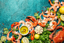 Fresh Raw Seafood - Shrimps And Crabs With Herbs And Spices On Turquoise Background. Copy Space