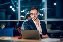 Attractive Businessman Smiling While Working With Laptop. Successful Wealthy Man With Glasses And Short Beard Working In Office Behind Computer Late In Evening.