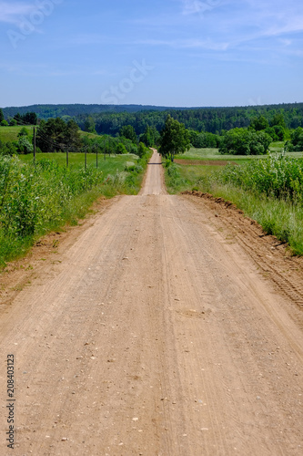 Foto op Canvas Zalm empty gravel road in the countryside in summer heat