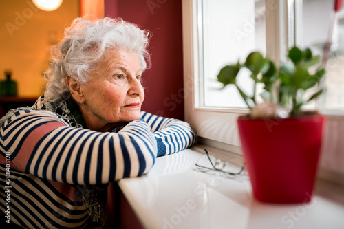 Sad alone senior woman looking through window