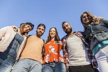 Gruppenfoto Von Fünf Guten Freunden. Alle Umarmen Sich Und Lächeln Freundlich In Die Kamera.