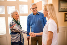 Smiling Positive Nurse Shake Hands With New Patients At Clinic