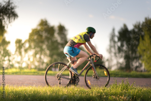 Cyclist man riding road sport bike in sunny day on a mountain road