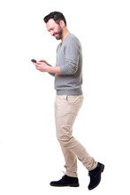 Full Length Side Of Man Walking With Mobile Phone