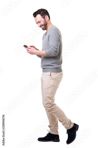 Full length side of man walking with mobile phone Wall mural