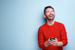 canvas print picture - cheerful man with mobile phone looking up