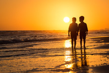 Silhouette Of Boys By The Ocean