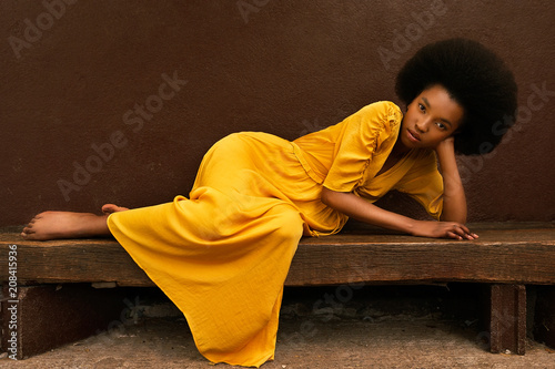 Portrait of a young woman lying on a wooden bench