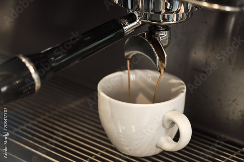 Coffee being poured to cup with professional machine