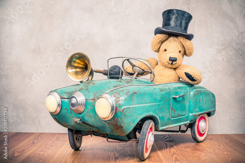 Keuken foto achterwand Vintage cars Teddy Bear in old antique cylinder hat driving rusty retro turquoise toy pedal car from circa 60s with classic brass klaxon in front concrete textured wall background. Vintage style filtered photo