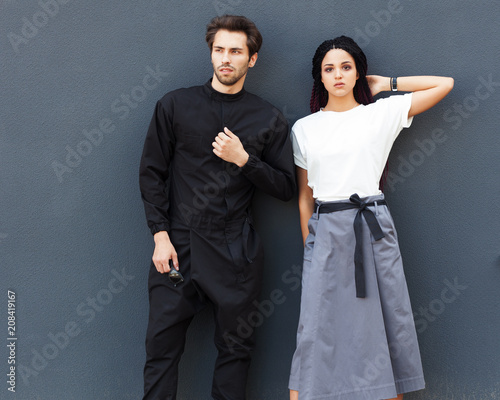 Beautiful young couple posing in a summer cool outfit. Youth street fashion. Overalls, T-shirt, long skirt. Wall mural