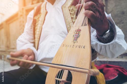 Fotografia  Man Plays Croatian Musical Instrument in Dubrovnik