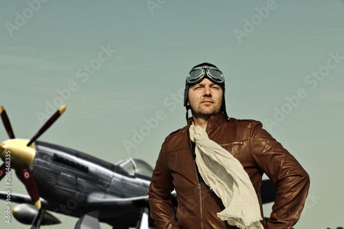 Portrait of a vintage pilot with leather cap, scarf and aviator glasses in front Canvas Print