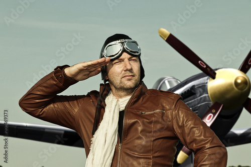Canvas Print Portrait of a vintage pilot with leather cap, scarf and aviator glasses salutes