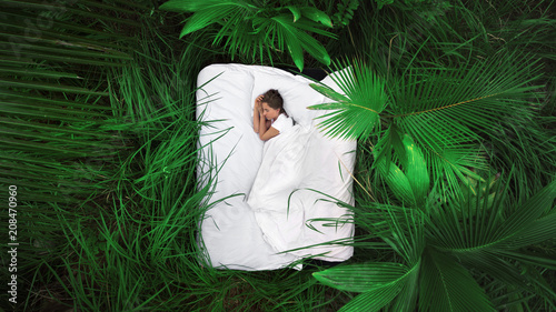 In de dag Spa A hidden place. Sleeping woman in deep jungle forest lies on airbed,View from above