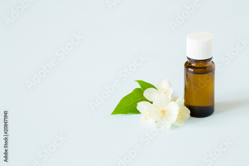 Small brown glass bottle on pastel blue table essential oil with small brown glass bottle on pastel blue table essential oil with jasmine blossoms mightylinksfo