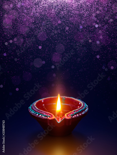 Diya lamp with glitter light background