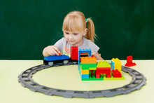 Girl Playing With A Train On A Chalkboard Background.