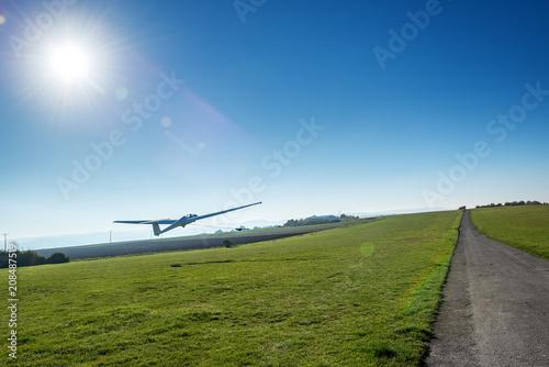startendes Segelflugzeug gegen die Sonne