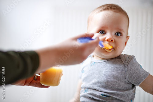 Obraz Mother feeds baby with fruit porridge - fototapety do salonu