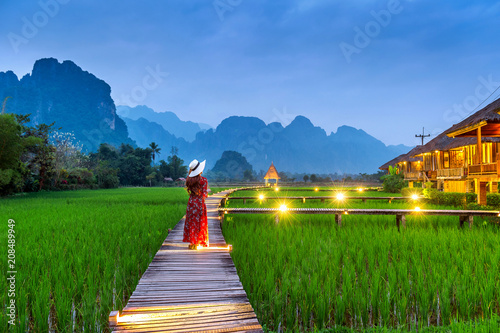 Photo Young woman walking on wooden path with green rice field in Vang Vieng, Laos