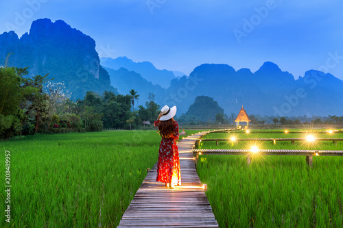 Foto auf AluDibond Grun Young woman walking on wooden path with green rice field in Vang Vieng, Laos.