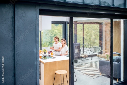 View through the window on the modern house interior with young couple eating indoors