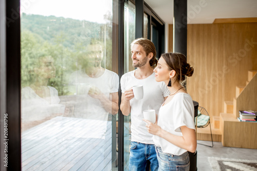 Obraz Young and happy couple dressed in white shirts standing together with cups near the window at home - fototapety do salonu