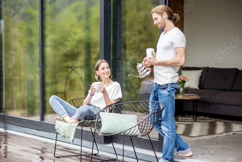 Fotografia Young couple sitting with cups on the terrace of the modern house enjoying beaut