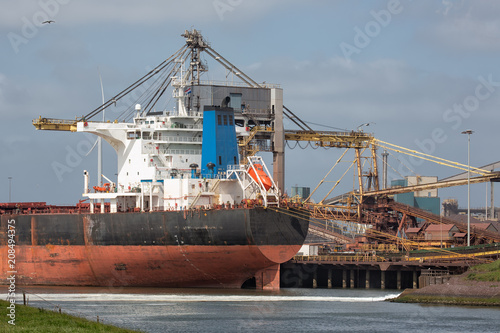 Valokuva  Big steel factory in harbor IJmuiden with cargo carrier in front, The Netherland