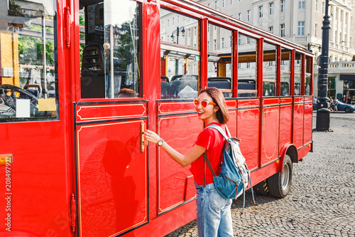 Foto op Canvas Londen rode bus Woman passenger sits in a retro red tourist bus to the sights of the European city