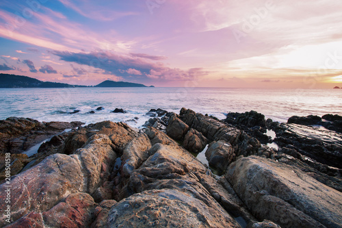 Photographie  Long exposure image of Dramatic sky seascape with rock in sunset scenery background